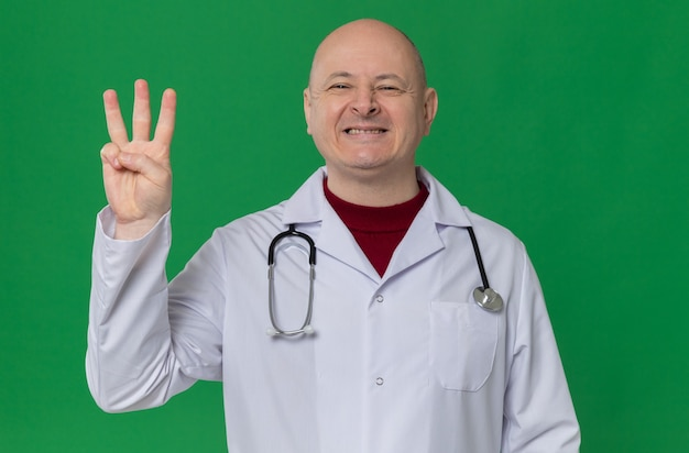 Smiling adult slavic man in doctor uniform with stethoscope gesturing three with fingers