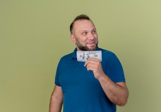 Улыбающийся взрослый славянский мужчина держит деньги, глядя на сторону