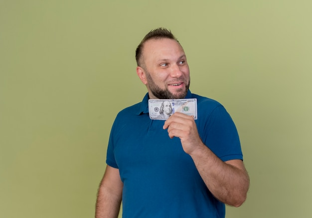 Smiling adult slavic man holding money looking at side