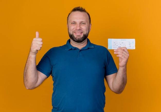Sorridente uomo slavo adulto in possesso di biglietto di viaggio cercando di mostrare il pollice in su