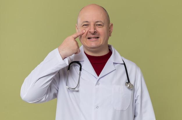 彼のまぶたに指を置く聴診器で医者の制服を着た大人のスラブ人の笑顔