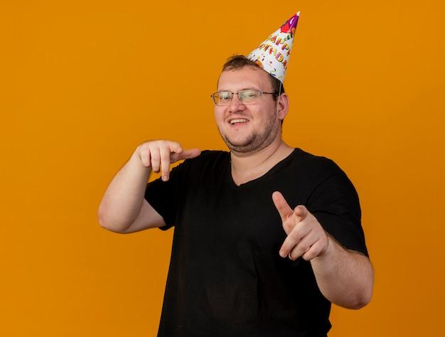 誕生日の帽子をかぶった光学眼鏡をかけた笑顔の大人のスラブ人がカメラを見て、指さしている