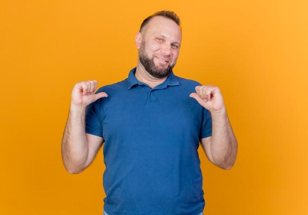 Sorridente uomo adulto slavo guardando e indicando se stesso isolato