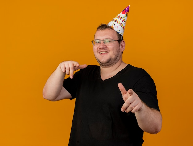 Smiling adult slavic man in optical glasses wearing birthday cap looks and points at camera
