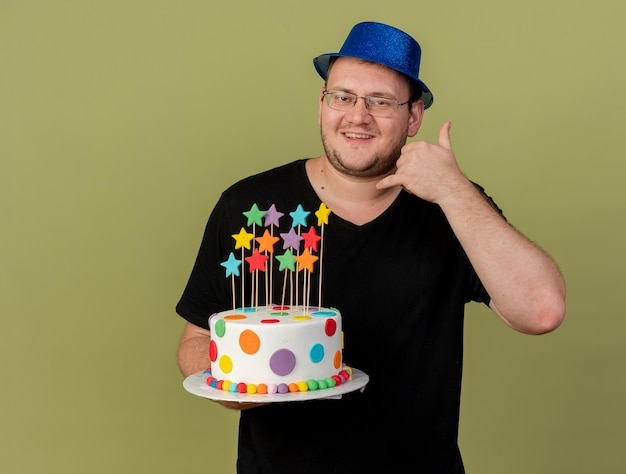 Smiling adult slavic man in optical glasses wearing blue party hat holds birthday cake and gestures ok hand sign