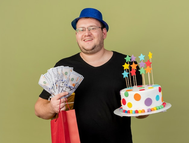 Smiling adult slavic man in optical glasses wearing blue party hat holds money gift box paper shopping bag and birthday cake