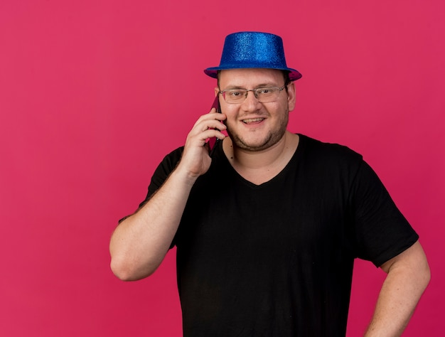 Sorridente uomo slavo adulto in occhiali ottici che indossa un cappello da festa blu parla al telefono