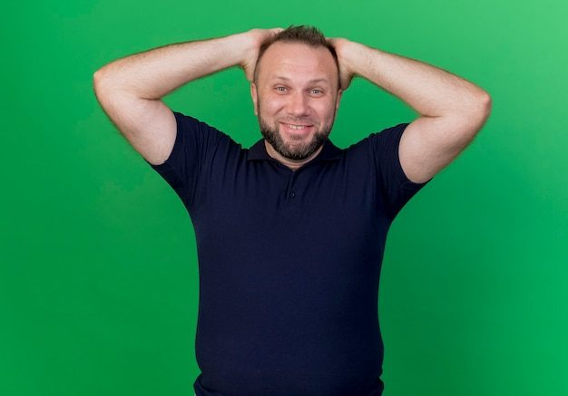 Uomo slavo adulto sorridente che mette le mani sulla testa che sembra isolato sulla parete verde
