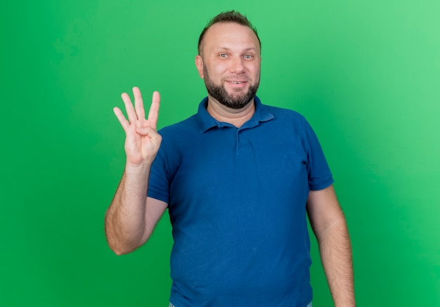 Smiling adult slavic man showing four with hand isolated on green wall with copy space