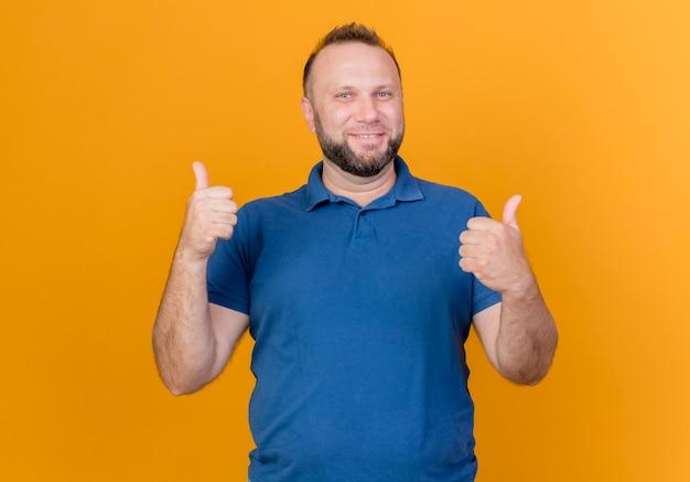 Uomo slavo adulto sorridente che mostra i pollici in su isolati