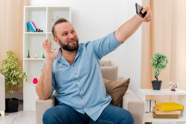 Sorridente uomo adulto slavo si siede sulla poltrona alzando la mano e guardando il telefono all'interno del soggiorno