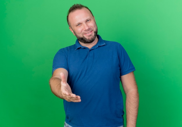 Улыбающийся взрослый славянский мужчина протягивает руку, делая приветственный жест, изолированный на зеленой стене с копией пространства