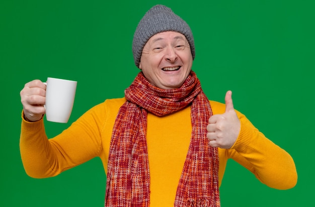 Smiling adult slavic man with winter hat and scarf around his neck holding cup and thumbing up