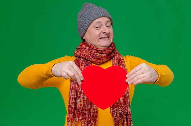 Smiling adult slavic man with winter hat and scarf around his neck holding and looking at red heart shape