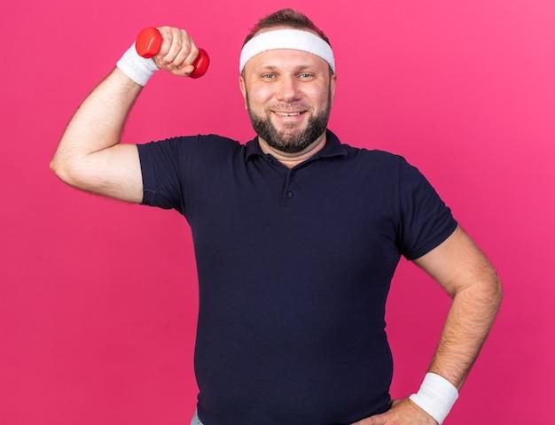 Улыбающийся взрослый славянский спортивный мужчина с головной повязкой и браслетами, напрягающий бицепсы, держащий гантели, изолированные на розовой стене с копией пространства