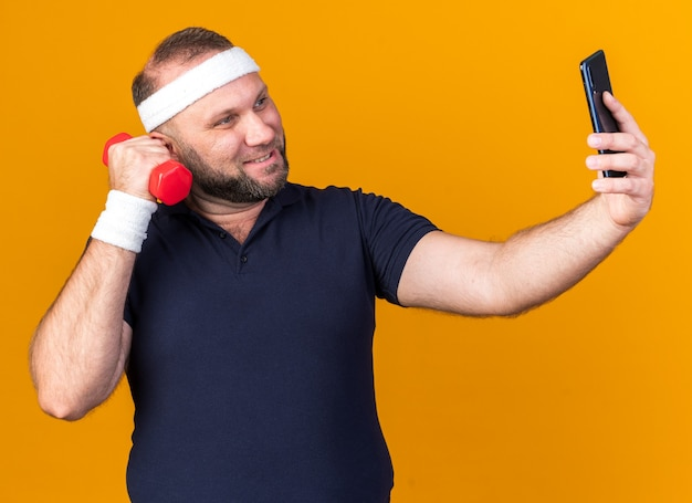 Smiling adult slavic sporty man wearing headband and wristbands taking selfie holding dumbbell isolated on orange wall with copy space