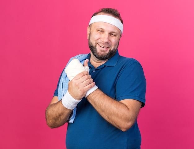 Улыбающийся взрослый славянский спортивный мужчина с полотенцем на плече, носящий повязку на голову и браслеты, держа его за руку, изолированную на розовой стене с копией пространства