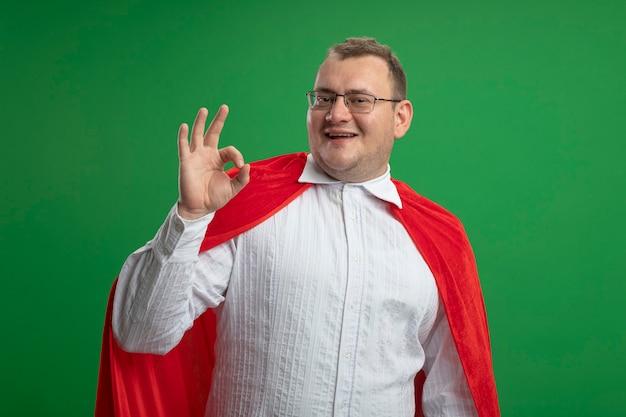 복사 공간 녹색 벽에 고립 된 확인 표시를 하 고 안경을 쓰고 빨간 케이프에서 성인 슬라브 슈퍼 히어로 남자 미소