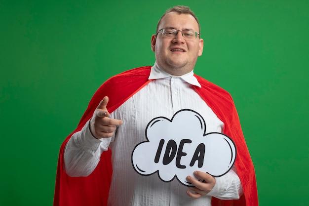 緑の壁に分離されたアイデアの泡を探して指している眼鏡をかけている赤いマントで笑顔の大人のスラブのスーパーヒーローの男