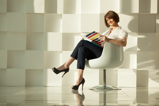 Smiling adult woman reading magazine in chair