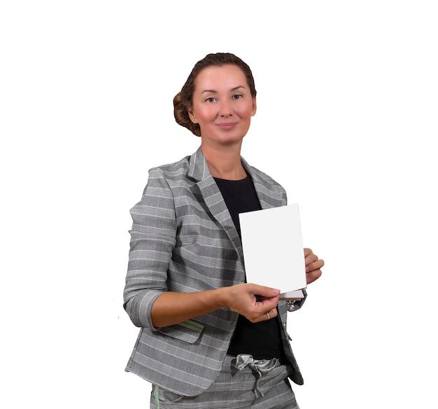 Улыбается взрослая женщина, показывая книгу или брошюру, изолированные на белом фоне
