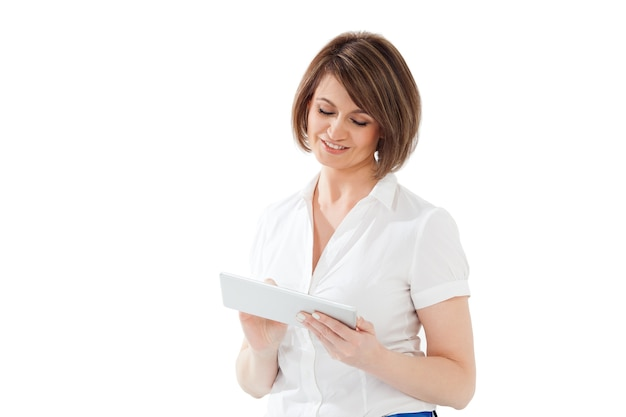 Smiling adult woman using tablet