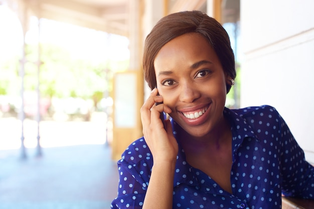 Smiling african american business woman using cell phone