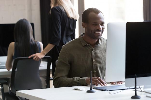 彼のコンピューターに取り組んでいる笑顔のアフリカ系アメリカ人実業家