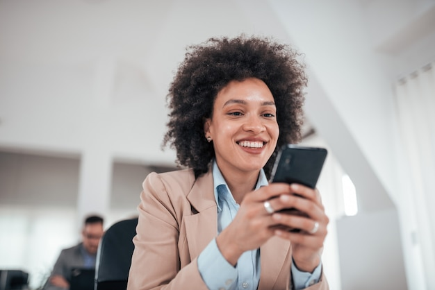 Smiling african american businesswoman using smart phone in co working office, low angle view.