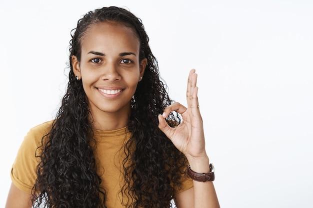 大丈夫、承認ジェスチャーを示す笑顔のアフリカ系アメリカ人の縮れ毛の女の子