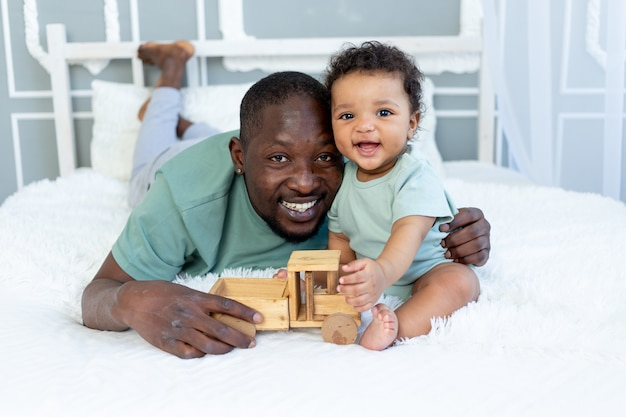 Smiling african american dad with baby son playing on the bed at home with wooden toy car, happy family