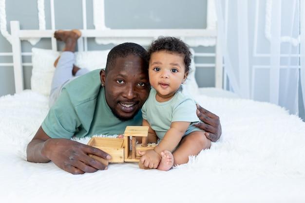 나무 장난감 자동차, 행복한 가족, 아버지의 날과 함께 집에서 침대에서 노는 아기 아들과 함께 웃고 있는 아프리카계 미국인 아빠