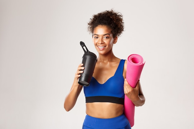 Smiling african-american female athlete, looking satisfied after workout, drinking water from bottle