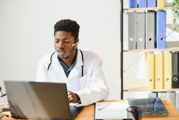 웃는 아프리카 계 미국인 여성 의사 gp는 직장에서 랩톱 컴퓨터를 사용하여 흰색 의료 코트를 착용합니다.