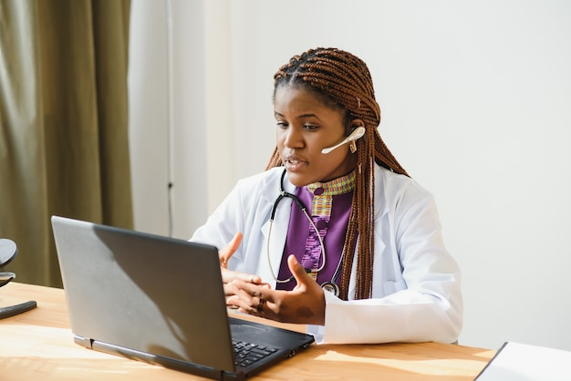 Smiling african american female doctor gp wears white medical coat using laptop computer at workplace gives remote online consultation.