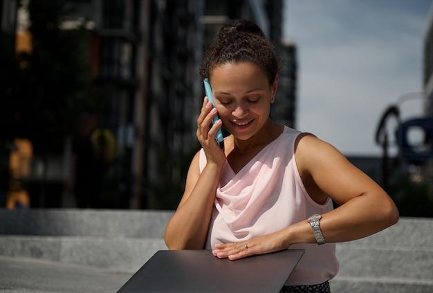 웃고 있는 아프리카계 미국인 프리랜서 여성이 도시 배경의 계단에 앉아 노트북을 사용하여 휴대전화로 통화하고 있습니다. 프리랜서, 비즈니스, 전자 학습, 온라인 회의 및 원격 작업 개념