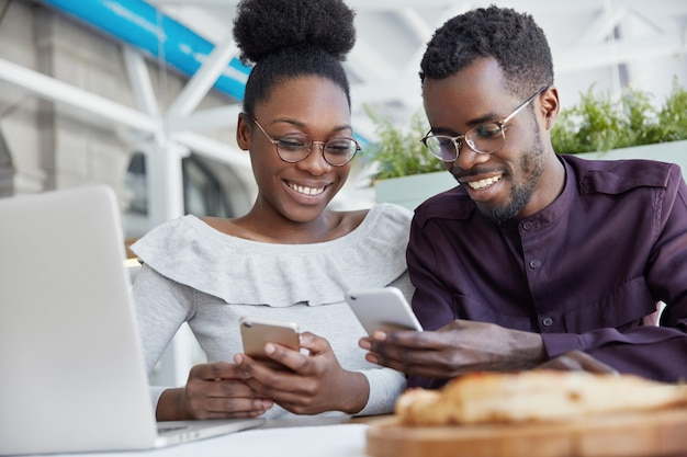 Smiling african american friends meet together at cafe, use modern technologies for entertainment. dark skinned delighted young female and male hold smart phones