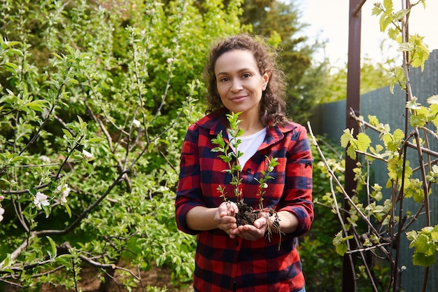 정원 나무 표면에 서 있는 손에 흙이 있는 민트 콩나물을 들고 웃고 있는 아프리카계 미국인 정원사 프리미엄 사진