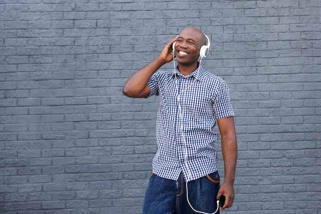 Smiling african american guy listening to music on headphones