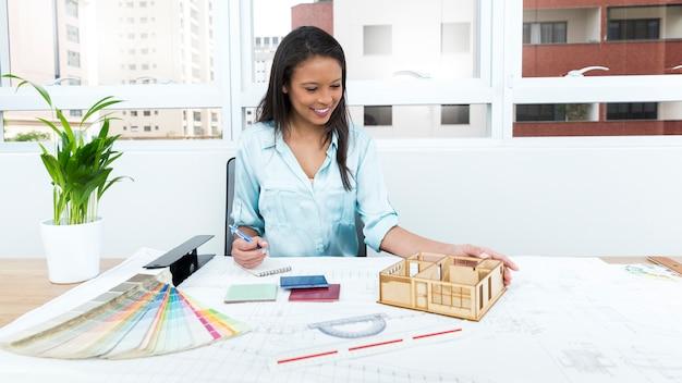 Улыбающаяся афроамериканская леди на стуле, делающем заметки около плана и модели дома на столе