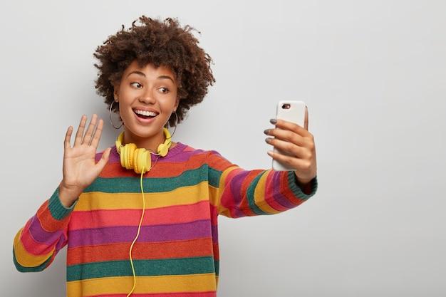 Sorridente signora afroamericana parla tramite videochiamata distante, saluta la telecamera, saluta un amico, indossa un maglione colorato a strisce