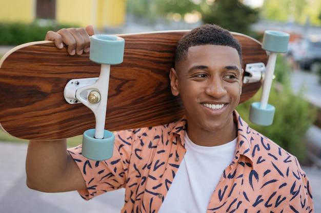 Улыбающийся афро-американский мужчина держит скейтборд портрет красивого стильного фигуриста на улице