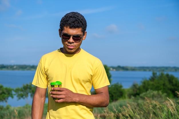 선글라스를 끼고 웃고 있는 아프리카계 미국인 남자는 여름에 강가에서 야외에서 커피 맛을 즐기고 카메라 앞에 서서 보고 서 있습니다. 복사 공간