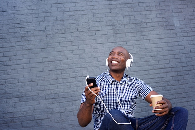 Smiling african american man listening to music on headphones