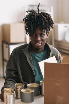 자선 및 기부 행사에서 자원 봉사하는 동안 통조림 식품을 상자에 포장하는 웃는 아프리카계 미국인 남자