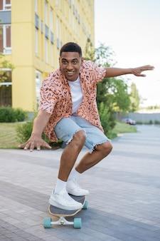 Улыбающийся афро-американский мужчина катается на скейтборде на улице, развлекаясь концепции активного образа жизни