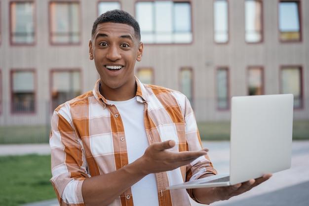 Улыбающийся афро-американский мужчина делает покупки в интернете с распродажами в черную пятницу, указывая рукой на ноутбук