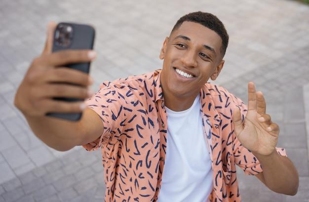 Улыбающийся афро-американский мужчина с помощью мобильного телефона онлайн счастливый турист, делающий селфи