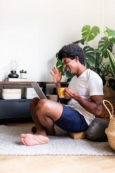 笑顔のアフリカ系アメリカ人男性が自宅でコーヒーとラップトップを使用してビデオ通話でこんにちはを振る垂直