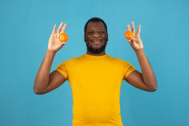 Улыбающийся афро-американский мужчина с мандарином в обеих руках стоит над синей стеной.